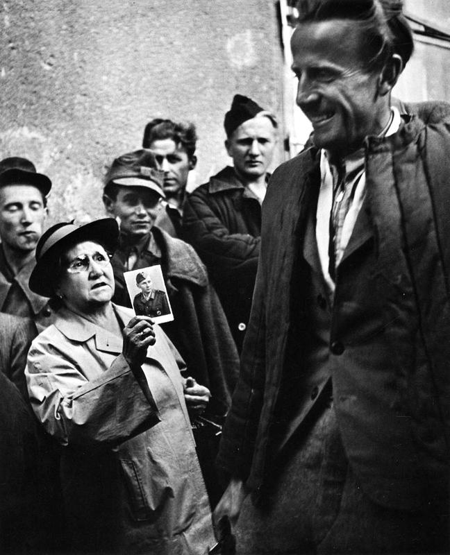 A mother shows a picture of her son to a returning  prisoner of war, 1947 (1)